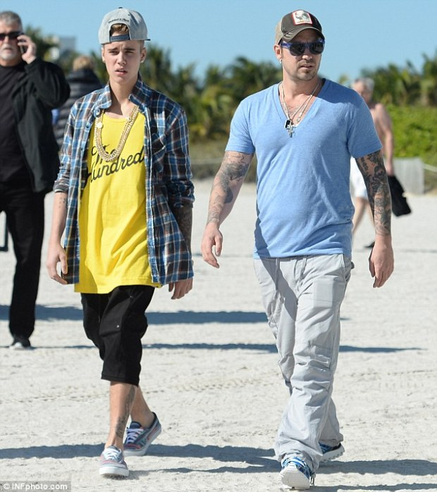 Guiding hand: Justin's father Jeremy Bieber arrived to spend the day with him on the beach