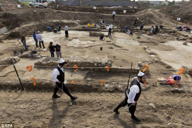 Jewish men who study in a nearby 'yeshiva' or religious seminary, pass by the large Byzantine era church that archaeologists have uncovered. Archaeologists believe the church was an important part of a Byzantine settlement which lay on the main road running between Jerusalem and the ancient sea port of Ashkelon