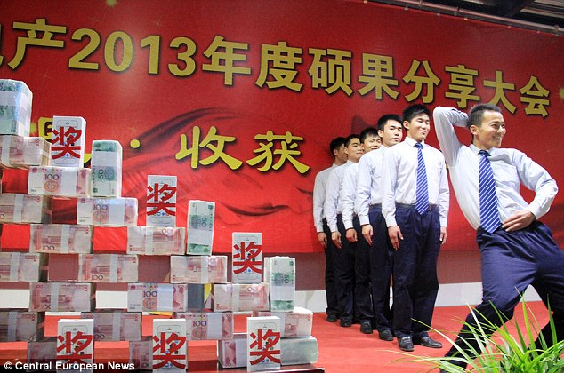 Wolf of Wall Street China-style: Workers dance next to a huge pile of cash