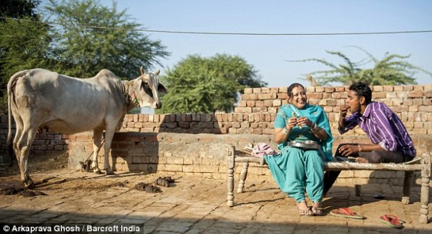 Home from home: Adriana Peral, pictured with her husband Mukesh Kumar while enjoying their lunch at their house in a village in Panipat, India, says she has no regrets about leaving California