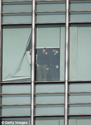 People look out of the window of the J P Morgan building at Canary Wharf