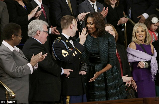 Presidential address: First lady Michelle Obama greets U.S. Army Ranger Sgt. First Class Cory Remsburg (3rd from L), injured while serving in Afghanistan, as she arrives prior to President Barack Obama's State of the Union speech