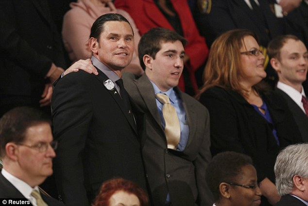 Strong: Boston Marathon bombing survivor Jeff Bauman, who had to have both his legs amputated after being injured in the blasts, stands with his rescuer Carlos Arredondo (L) before the start of U.S. President Barack Obama's State of the Union speech