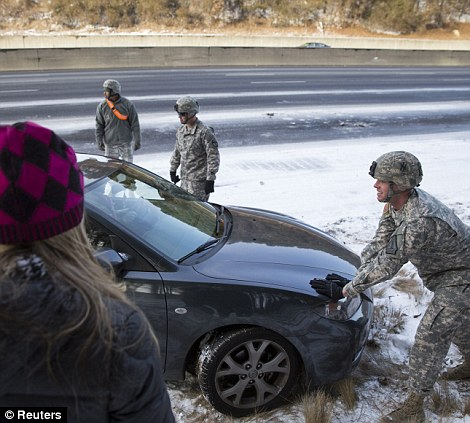 Georgia National Guard Sgt. Chad Armstrong (right) and other guardsmen help people get their stranded cars out of the snow in Atlanta