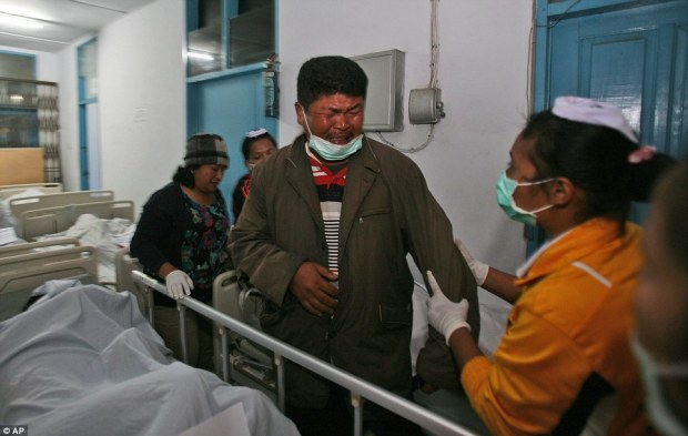 Distraught: A man weeps after identifying a family member killed by the eruption in Kabanjahe, Sumatra