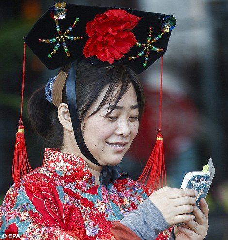 Ancient celebrations in a modern age: A woman dressed in traditional imperial costume uses a mobile at a department store in Beijing during New Year celebrations