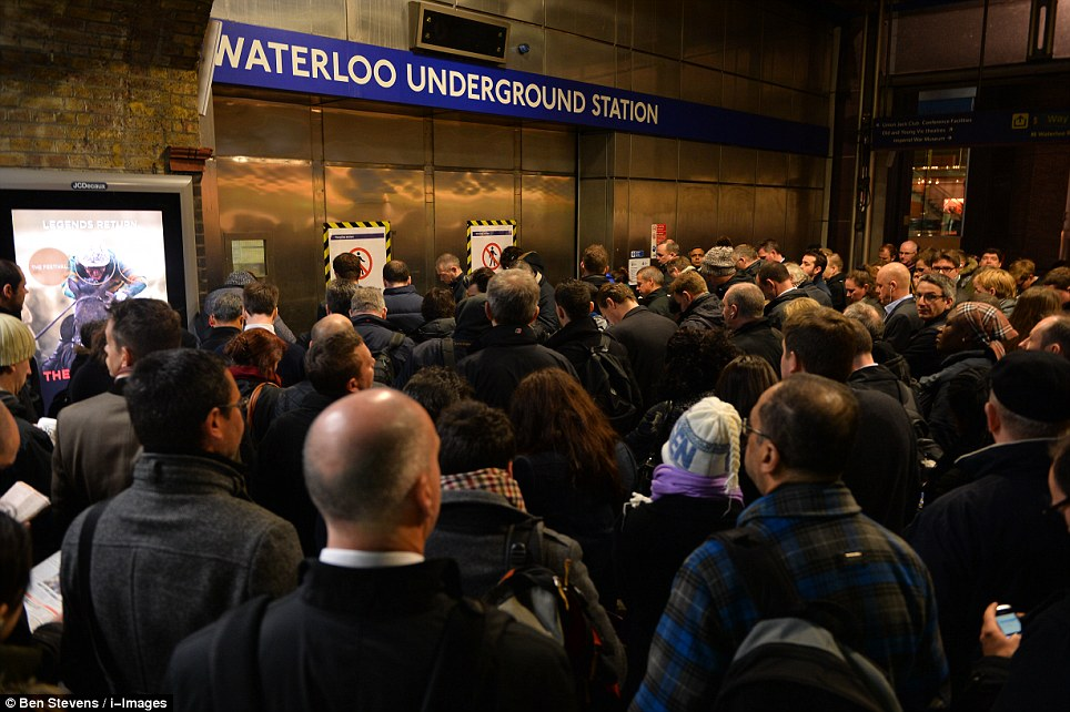 Travel chaos: Commuters queue outside the underground station as a tube strike over ticket office closures caused chaos across London