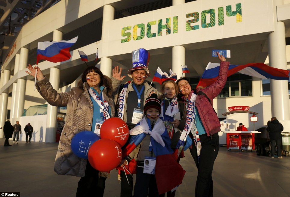 Russian pride: Local fans wave as they arrive at the stadium for the opening ceremony of the 2014 Sochi Winter Olympics