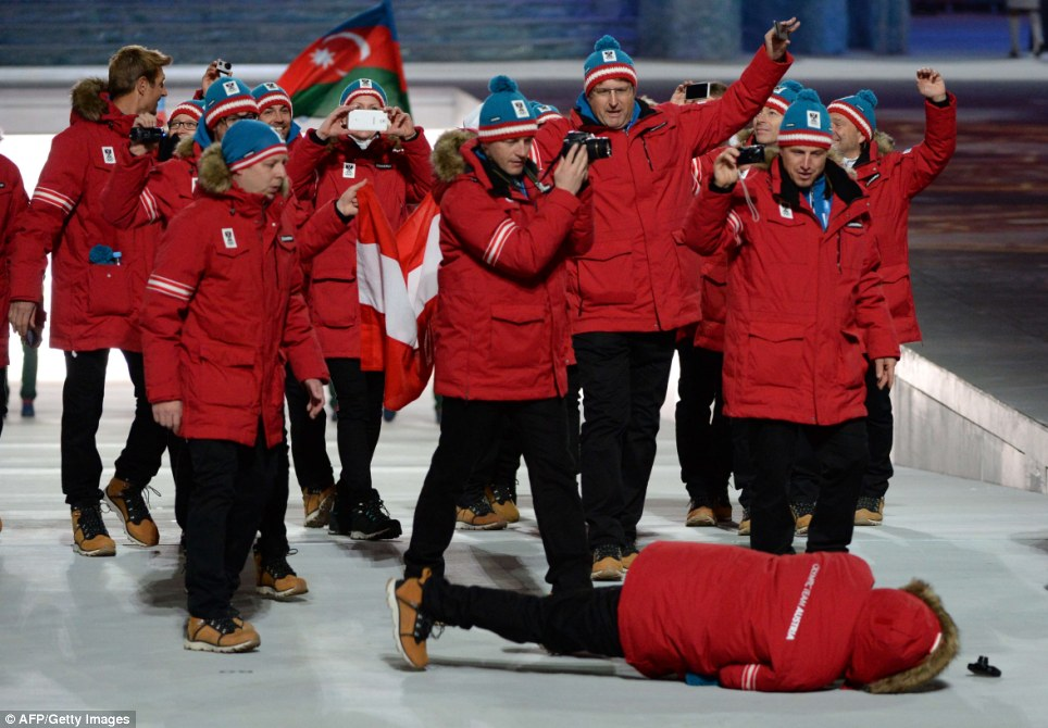 What a trip: A member of Austria's delegation lies on the ground after falling over in the middle of the stadium during the country's entry walk at the Opening Ceremony