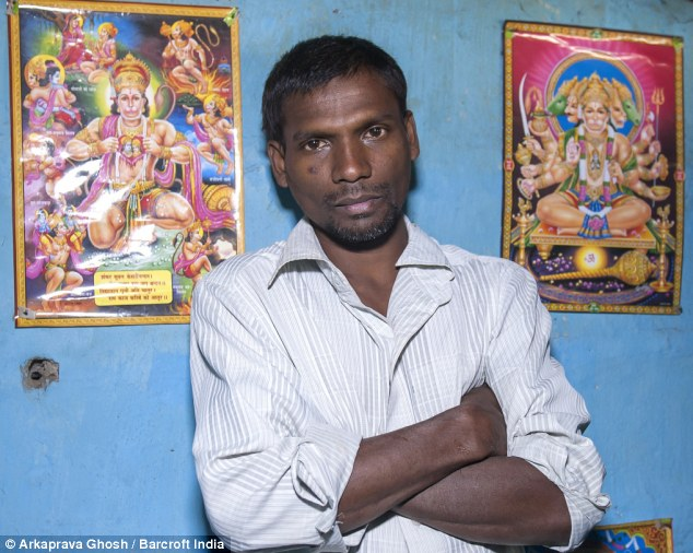 Family photo: Mr Oraon stands in front of posters showing Hanuman the Monkey God at a shrine in his house in Jalpaiguri, West Bengal