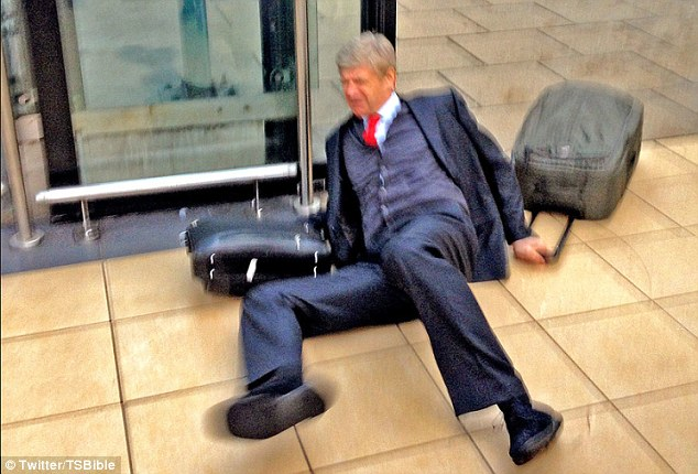 Slipped up: Wenger looks in pain as he takes a tumble coming into the station