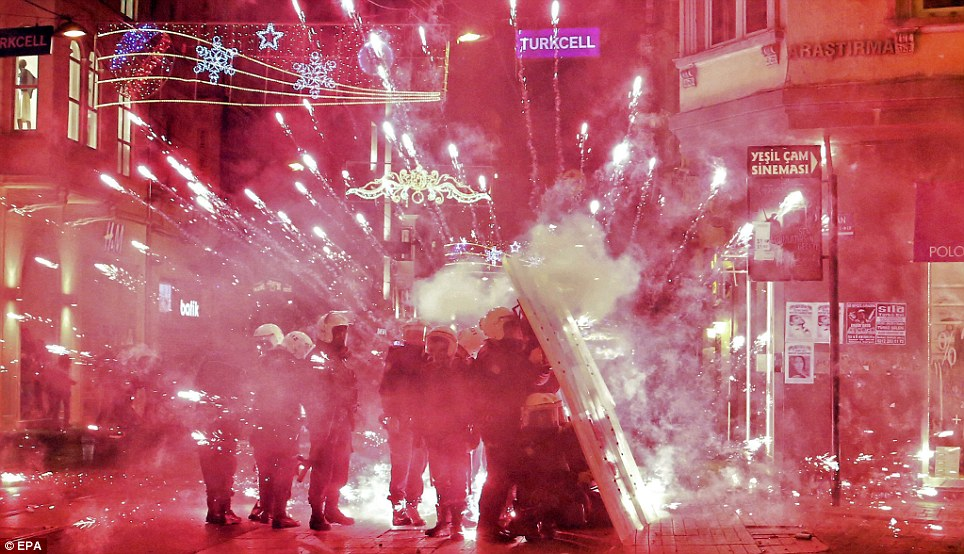 Anger: Turkish riot police take cover behind their shields as fireworks explode in front of them during clashes with anti-government protestors