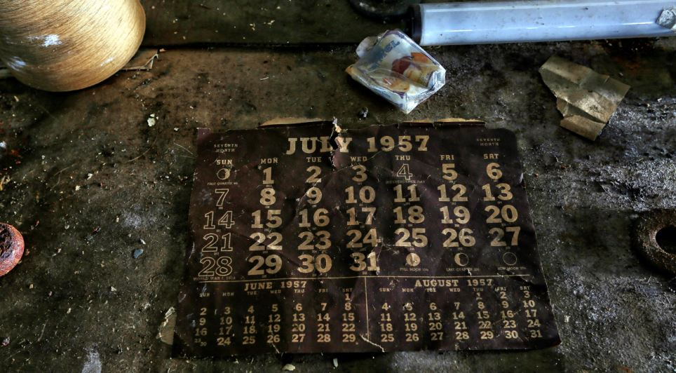 Another calender showing July 1957 sits on the factory floor surrounded a discarded Camel cigarette packet. The factory closed its doors for the final time that month