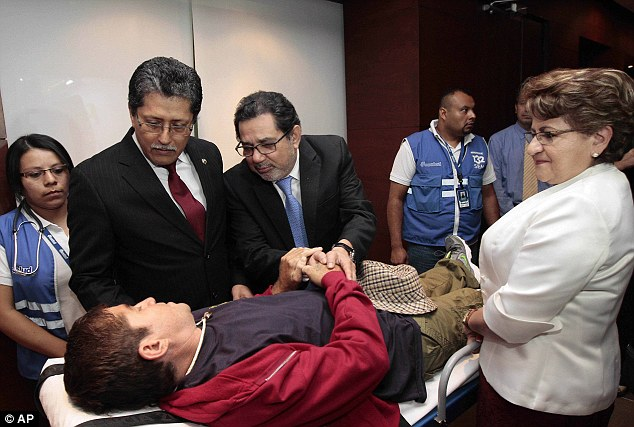 Foreign Minister Jaime Miranda (second left) Vice Foreign Minister Juan Jose Garcia (center) and Vice Minister of Health Violeta Menjivar (right) greet Jose Salvador Alvarenga, who lies on a stretcher after arriving at the airport in San Salvador, El Salvador, on Tuesday