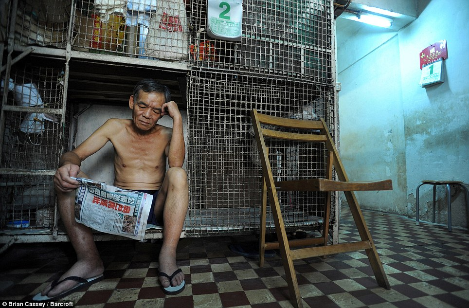 Life in a cage: Yan Chi Keung, 57, reads the newspaper in his cage home in Hong Kong. The wire mesh boxes are 6ft long and up to 3ft wide and cost £117 a year, compared to £1,240 a month for a small, privately-rented one-bedroom apartment. More than 220,000 people are on the housing waiting list