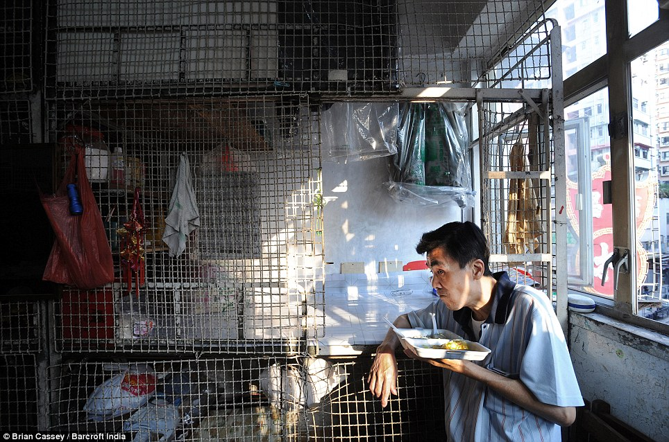 Dank: Former Chinese restaurant worker, 60-year-old Tang Man Wai, eats next to his cage home. It is impossible to know how many of the cages there are because so many of them are run illegally, including the one pictured. The estimated number shot from a few thousand in the early 1990s to 53,000 in 2007