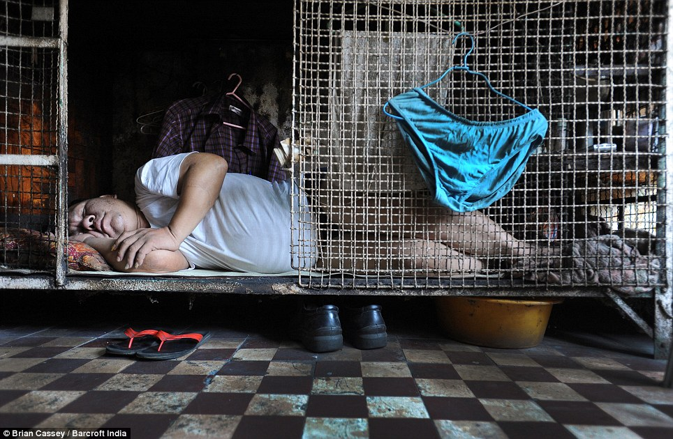 Caged dogs: Retired Kong Sui Kao, 64, lives in this cage in a cramped room alongside seventeen other people on the roof of a 12-storey block. His underwear hangs on a coat hanger, his shirts are inside the cage and his meagre possessions are stored on a makeshift shelf above his feet