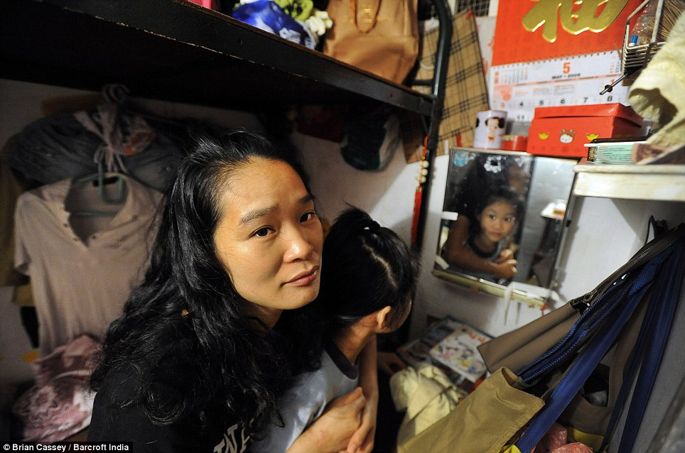 Poverty: Eight-year-old Lee Ka Ying lives in a 6ft square 'cubicle cage home' with her mother, pcitured. For many it is the only way to work in the overcrowded city