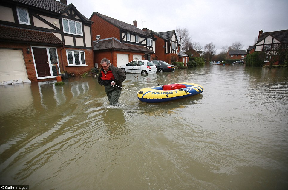 Water up to here: A resident pulls a boat towards his house in a flooded street on Friday near Staines-Upon-Thames, England. Flood water has remained high in some areas and high winds are causing disruption to other parts of the UK with the Met Office issuing a red weather warning
