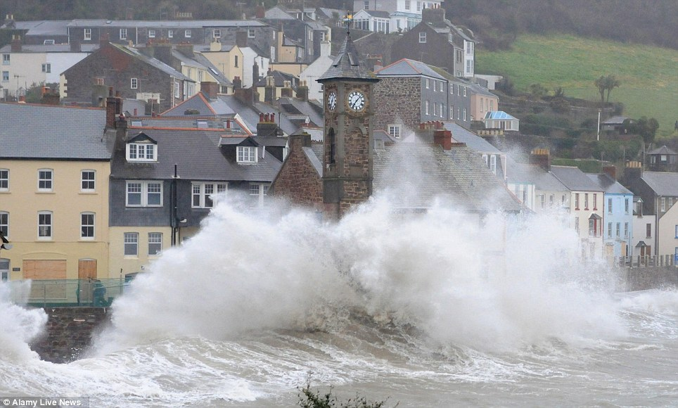 Wild waves: Wind, rain and waves batter the Cornish village of Kingsand in England on Friday as the environment agency warns hundreds more homes will be flooded this weekend