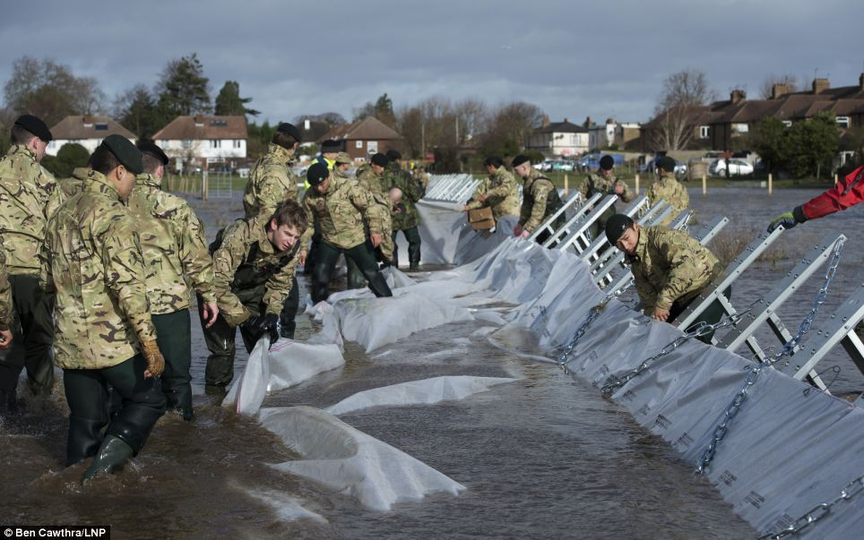 Soldiers from 2nd Royal Tank Regiment and The Gurkhas   installing Geodesign flood barriers in Staines, which have been brought in from Sweden to help control flood waters