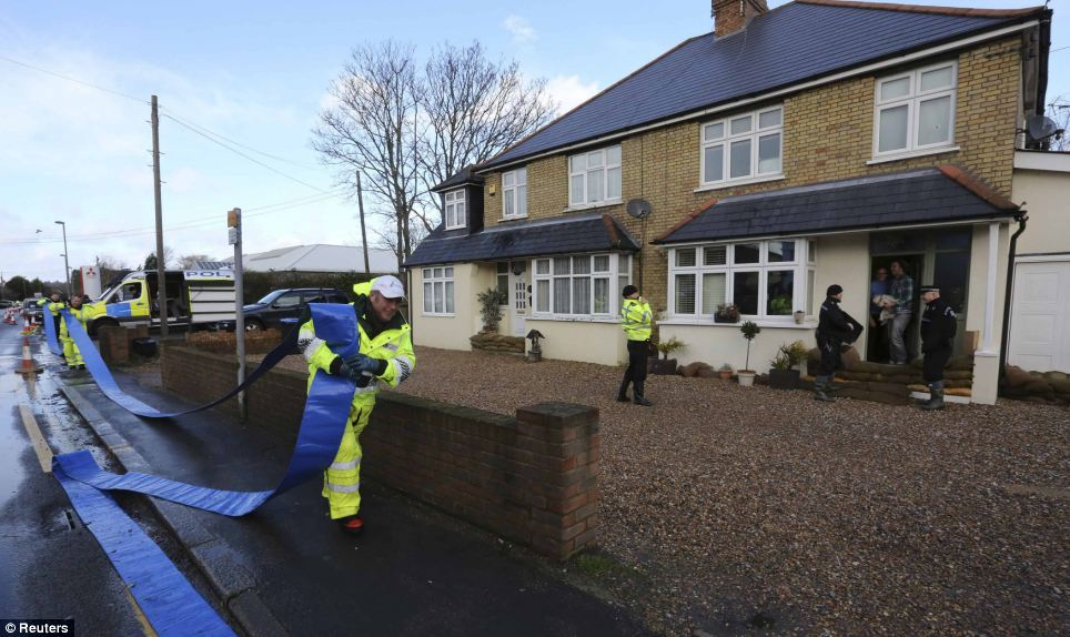 Environment agency staff move a pipe to help manage the flooding situation in Chertsey, southern England. Agencies and emergency services have been inundated with calls for help