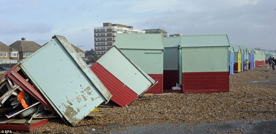 Beach huts lie shattered and twisted after gale force winds broke down a retaining wall at Hove during storms that lashed the south coast