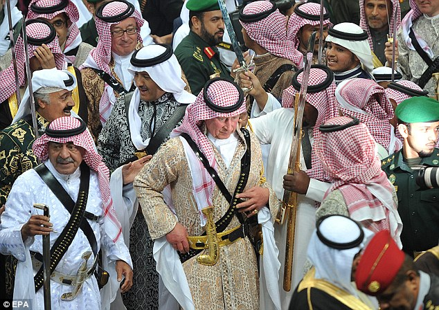 epa04086853 Britain's Prince Charles wearing traditional Saudi costume walks with Saudi second deputy Prime Minister Mugren bin Abdulaziz (left down), after the end of the traditional Saudi dancing