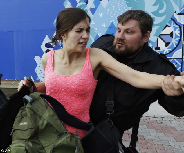 Nadezhda Tolokonnikova is pulled away by a Russian security officer. The group ran out of the restaurant wearing brightly colored clothes and ski masks and were immediately set upon by about a dozen Cossacks, who are used by police authorities in Russia to patrol the streets