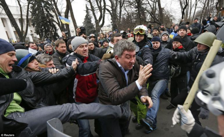 Anti-government protesters attack a deputy of the Party of Regions Vitaly Grushevsky (centre) outside the Ukrainian Parliament building