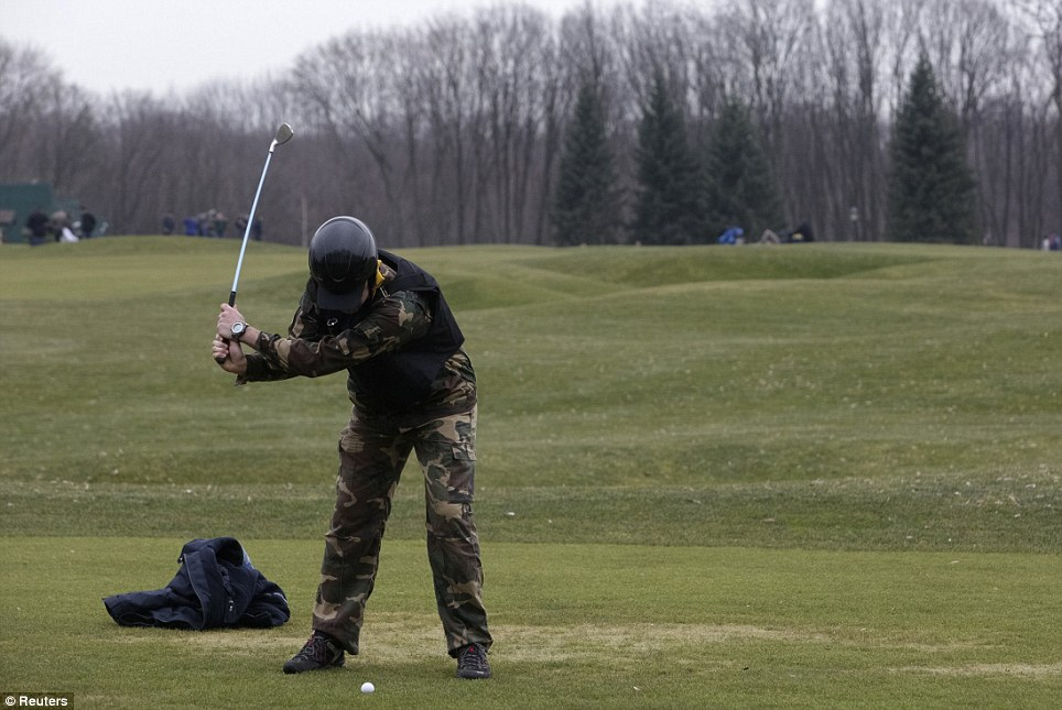 A man wearing a kevlar vest and combat trousers plays golf on the president's private course