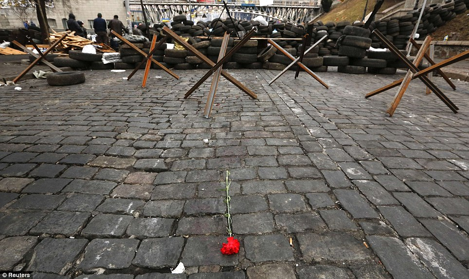 Sombre: A rose is left near a barricade put up by anti-government protesters in Kiev today