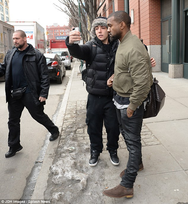 Fan unfriendly: Kanye West wore a stony face as a young fan approached him and started taking his picture as the rapper left his New York City pad on Tuesday