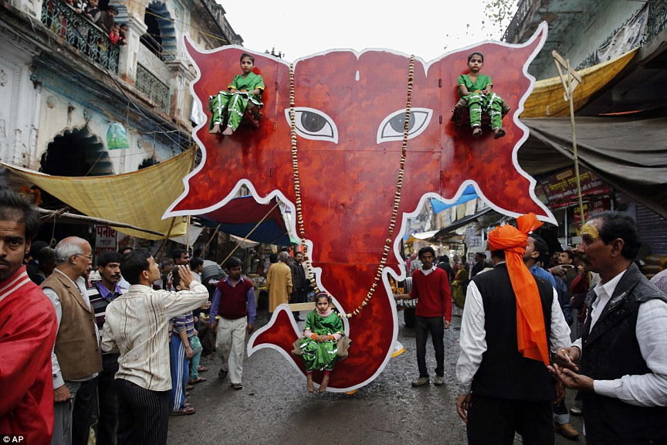 Parade: Three colourfully dressed little girls sit on a huge cut out portrait of an elephant head as they process through the streets of Allahbad