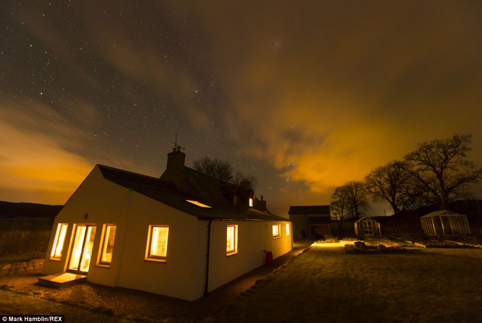 Beautiful: The Northern Lights are pictured over a house, garden and greenhouse in Carrbridge, Inverness-shire