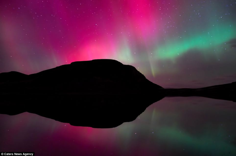Captivating: Skies over Loch Brora in the Scottish Highlands turn red and green by a mesmerising display of the Aurora Borealis