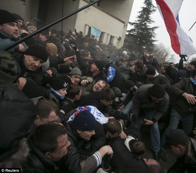 Ukrainian men help pull one another out of a stampede as a flag of Crimea is seen during clashes at rallies held by ethnic Russians and Crimean Tatars near the Crimean parliament building