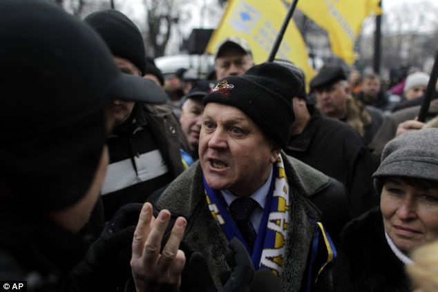Rage: An anti-Yanukovych protester argues in front of the Ukrainian parliament in central Kiev