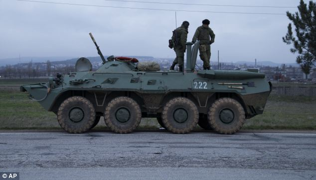 Two soldiers stand on top of a Russian armoured personnel carrier as it is parked on a road near Bakhchisarai, in the Crimea. The presence of RUssian armour on the move has raised tensions in the area, which has a majority Russian population.