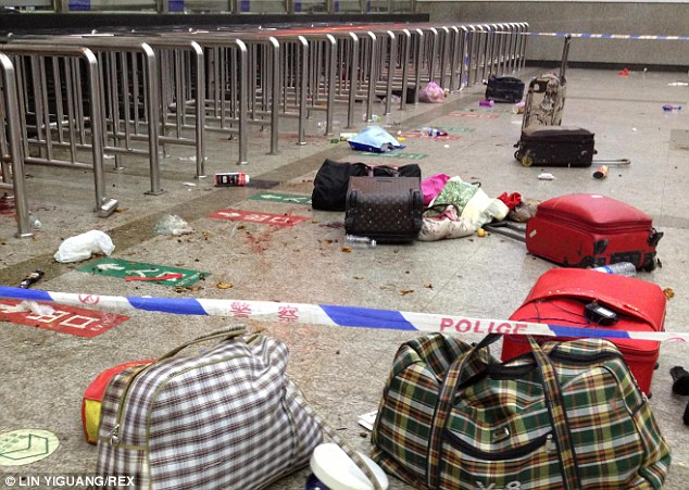 Abandoned: Travel bags surrounded by blood lie strewn across then floor of the terminal, protected by police