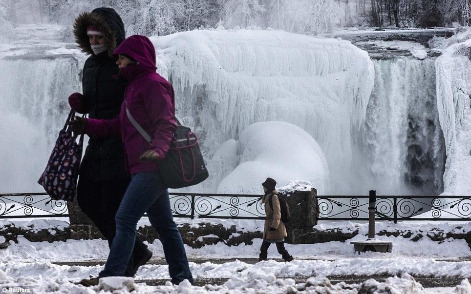 Agrupar-se: As pessoas caminham ao lado os EUA das Cataratas agasalhados para se proteger contra as temperaturas subfreezing