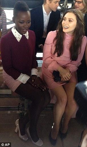 Fashion faces: Lupita sat alongside Elizabeth Olsen on the front row of the catwalk show