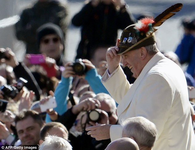The papa: Pope Francis joked with the crowd and even put on a military Alpine hat as the interview about his week-long love story was published
