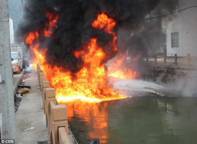 Blazing river: A lit cigarette set the water on fire, and flames shot up more than 16ft into the air before it was extinguished by firemen in Wenzhou in eastern China