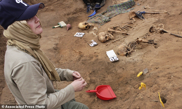 In this photo taken Tuesday, Feb. 18, 2014, volunteer Amber Barton, from the San Francisco area, works with colleagues from the Peruvian Forensic Anthropolog...