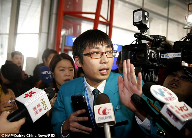 Information: A member of staff from Malaysia Airlines is surrounded by reporters at the airport