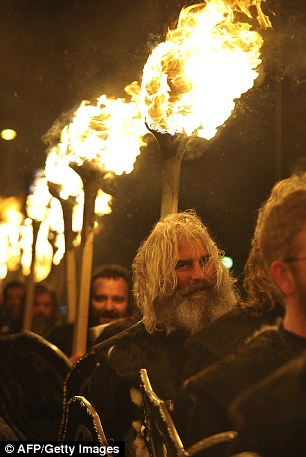 People dressed as Vikings carry burning brands as they take part in a Norse reconstruction festival