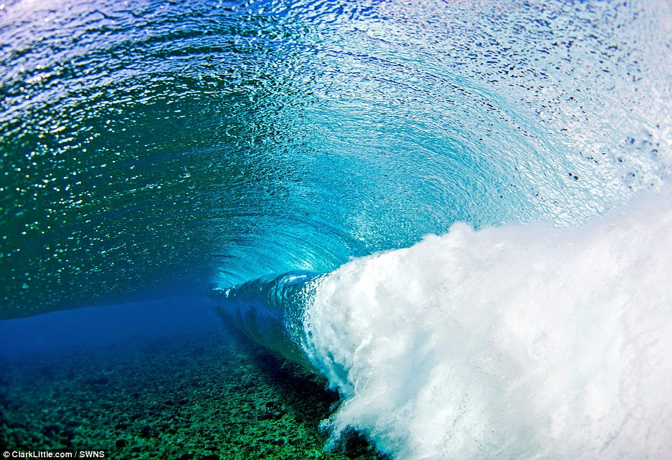 This picture was taken underwater from the backside of a Tahitian tube spinning down a shallow reef in Tahiti, French Polynesia
