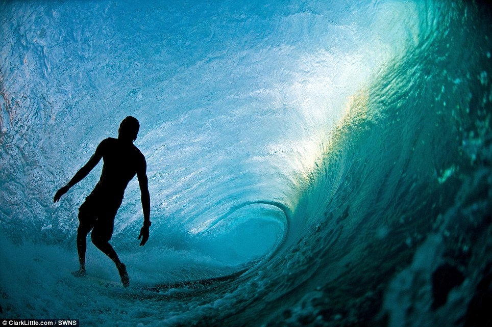 The silhouette of a surfer Flynn Novak is frozen the moment before he jumps off the back of his surfboard. The flash was supposed to go off and set the scene alight. Instead, the true light from inside the wave is perfectly captured