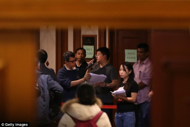 Malaysia Airlines staff organise relatives of passengers onboard Malaysia Airlines flight MH370 as they line up to receive a special condolence payment of 31,000 CNY (almost $5,000) at Lido Hotel, in Beijing